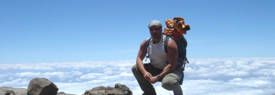 Me posing with backpack on, clouds below in the distant, as I climb Mt Kilimanjaro